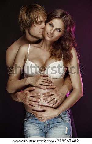 young pregnant couple isolated over black background - stock photo