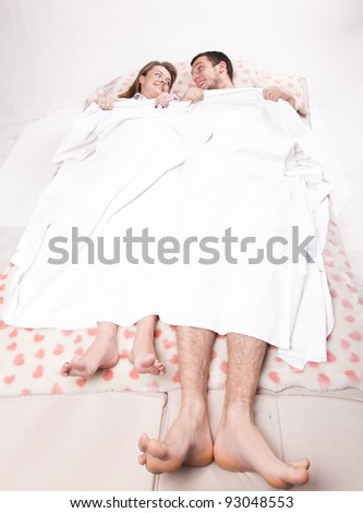 Young pregnant couple lying on bed under blanket - stock photo
