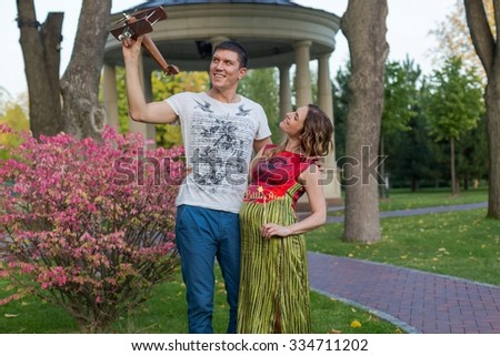 Young pregnant couple - plaing with toy airplane outdoor