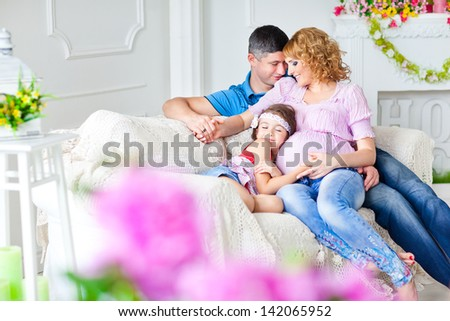 Young pregnant family relaxing on the sofa - stock photo
