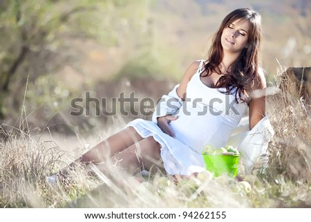Young pregnant girl is in the nature