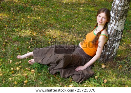 young pregnant girl sitting under a tree