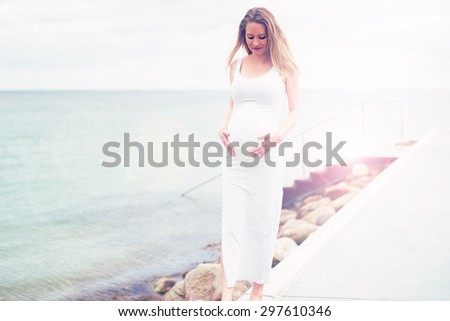 Young pregnant woman bonding with her unborn baby standing on a promenade overlooking the ocean cradling her swollen tummy in her hands, with copyspace in a healthy lifestyle concept - stock photo