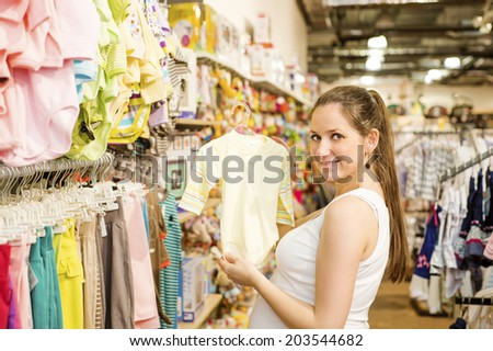 Young pregnant woman choosing baby clothes at baby shop store - stock photo