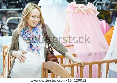 Young pregnant woman choosing cot or bassinet for newborn baby at infant shop - stock photo