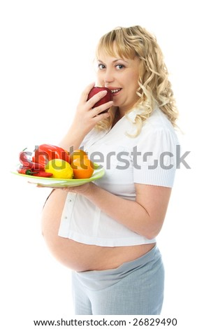 young pregnant woman eating an apple and holding oranges in her hands - stock photo