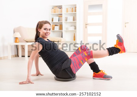 Young pregnant woman exercising with balance pillow at home - stock photo