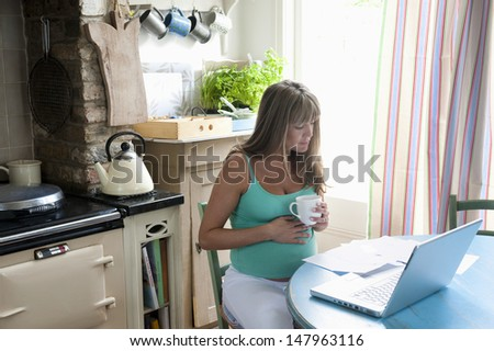 Young pregnant woman holding coffee cup with laptop and documents at kitchen table - stock photo