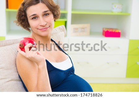 Young pregnant woman holding garnet - stock photo