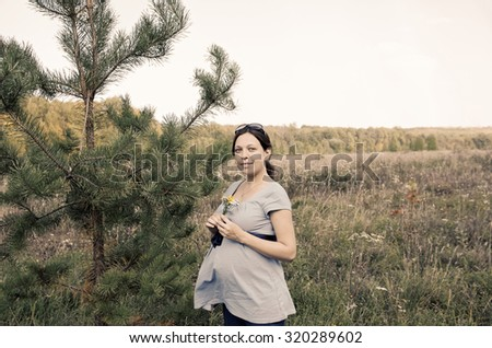 Young pregnant woman in field with a bunch of wild flowers. Selective focus. Photo taken at shady side. Sepia toned. - stock photo