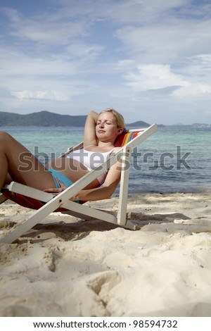 young pregnant woman lies in the deck chair on the beach