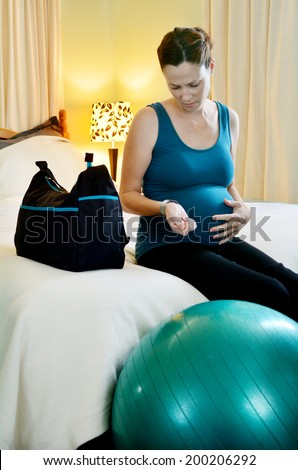 Young pregnant woman looking at her wrist watch, timing contraction pains and holding her tummy in her bedroom at home. - stock photo