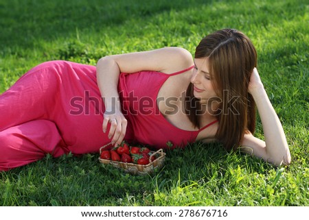 Young pregnant woman lying on grass with strawberry - stock photo