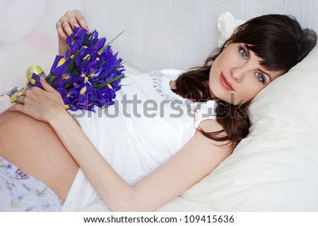 young pregnant woman lying on the sofa - stock photo