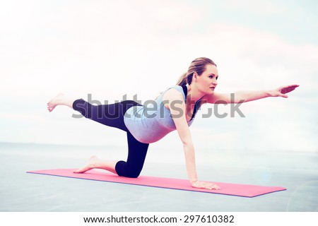 Young pregnant woman practicing pilates doing exercises to control and strengthen her muscles working out on a gym mat balancing outstretched on one knee - stock photo