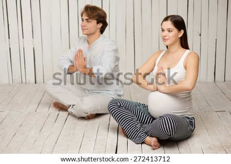 Young pregnant woman practicing yoga with her husband. They meditating in lotus position with folded hands - stock photo