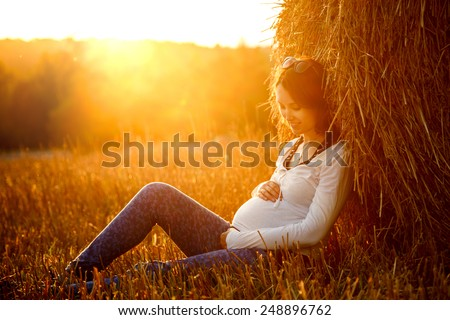 Young Pregnant Woman Sitting by the Haystack at Sunset and Embracing her Belly. 7 Month Pregnancy. Maternity Concept. Toned Photo.