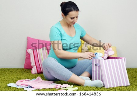 Young pregnant woman sitting on carpet and folding baby wear on wall background - stock photo