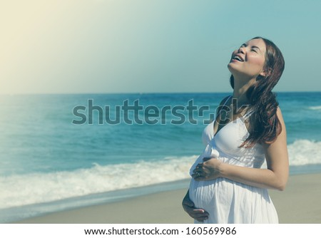 Young pregnant woman walking on the beach - stock photo