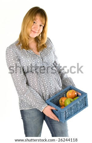 young pregnant woman with a basket full of apples - stock photo