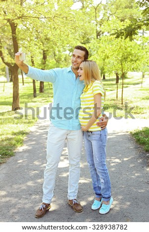 Young pregnant woman with husband making selfie in park