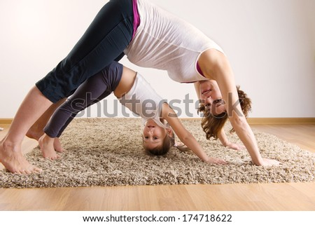 Young pregnant woman with little daughter doing yoga exercises