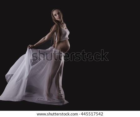 Young pregnant woman with plume on black background - stock photo