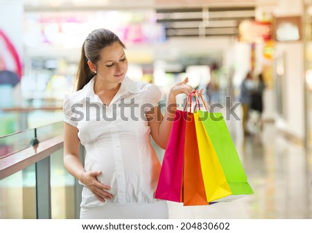 Young pregnant woman with shopping bags in shopping mall - stock photo
