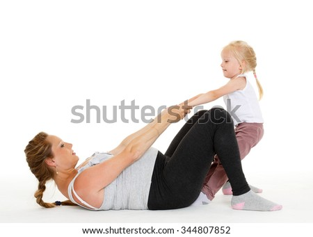 Young pregnant woman with small daughter are doing sports exercises on a white background. Healthy family. - stock photo