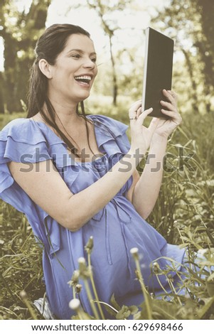 Young pregnant woman working on the tablet. Woman sitting on the grass and using digital tablet.