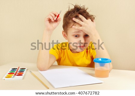 Young preoccupied artist in a yellow shirt is thinking what to paint - stock photo