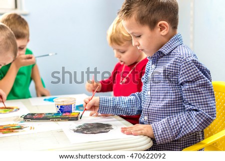 Young preschool kids painting and drawing in Kindergarten.
