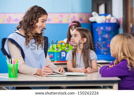 Young preschool teacher teaching little girls in classroom - stock photo