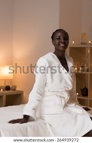 Young pretty african woman sitting at beauty spa salon wearing bathrobe - stock photo