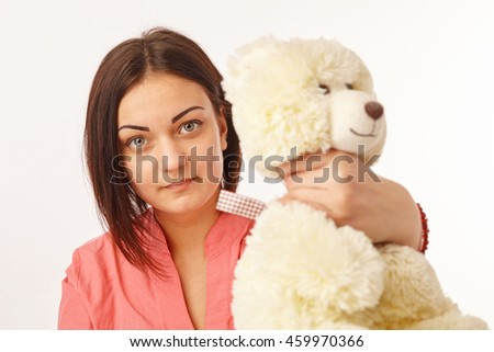 Young pretty angry girl strangling teddy bear