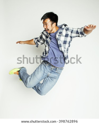 young pretty asian man jumping cheerful against white background, lifestyle people concept - stock photo