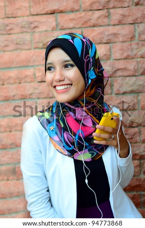 young pretty Asian muslim college girl with listen to music. - stock photo