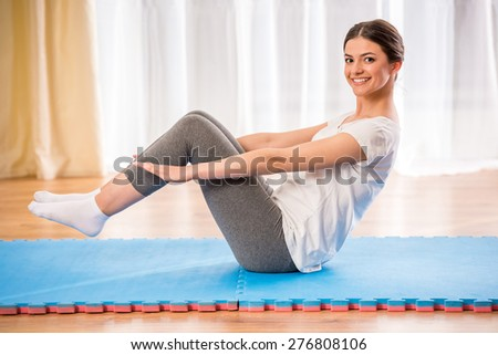 Young pretty athletic girl doing fitneaa on a rug at home.