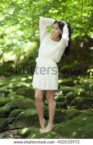 Young pretty attractive girl posing in nature, white dress, wreath of flowers, portrait
