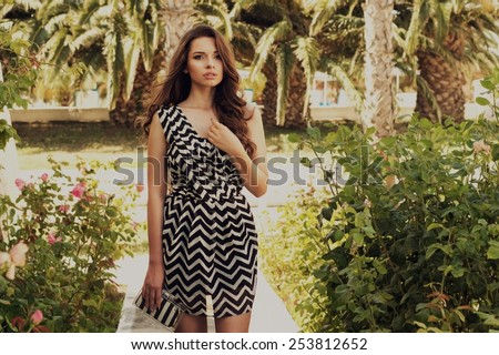 Young pretty beautiful stylish girl with dark long curly hair, wearing sexy minidress and holding fashionable handbag - stock photo