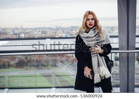 Young pretty blond woman standing in modern interior with aerial view on the city of Berlin.