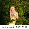 Young pretty blonde woman harvesting outdoors - stock photo