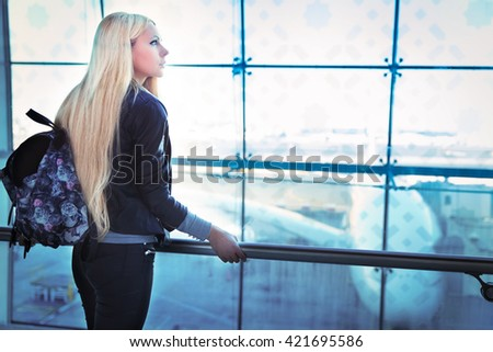 Young pretty blonde woman looking into window in airport