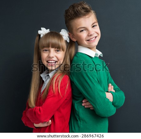 Young pretty boy and girl posing at the black chalkboard in classroom. Photo of boy 11 years old. Photo of girl 9 years old.  - stock photo