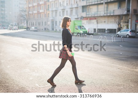 young pretty brown hair woman walking trough the streets using a smartphone, overlooking left, dressed with a checked skirt and a black sweater - relaxing, technology, social network concept - stock photo