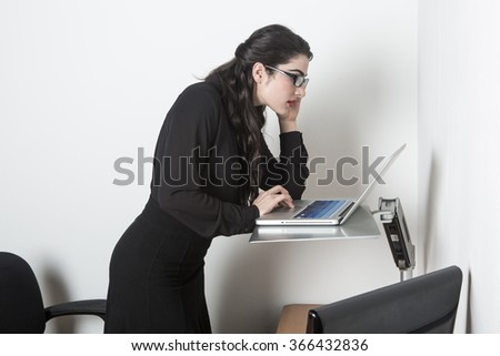 Young pretty business woman standing up using computer in the office