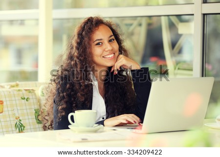 Young pretty business woman with laptop in the restaurant - stock photo