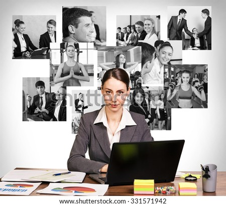 Young pretty business woman with notebook in the office and collage on the wall - stock photo