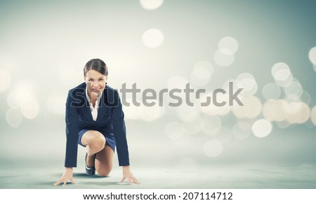 Young pretty businesswoman in suit ready to run
