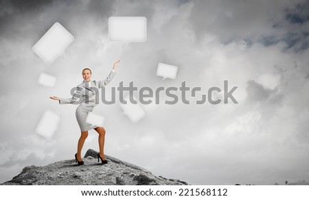 Young pretty businesswoman juggling with speech bubbles - stock photo
